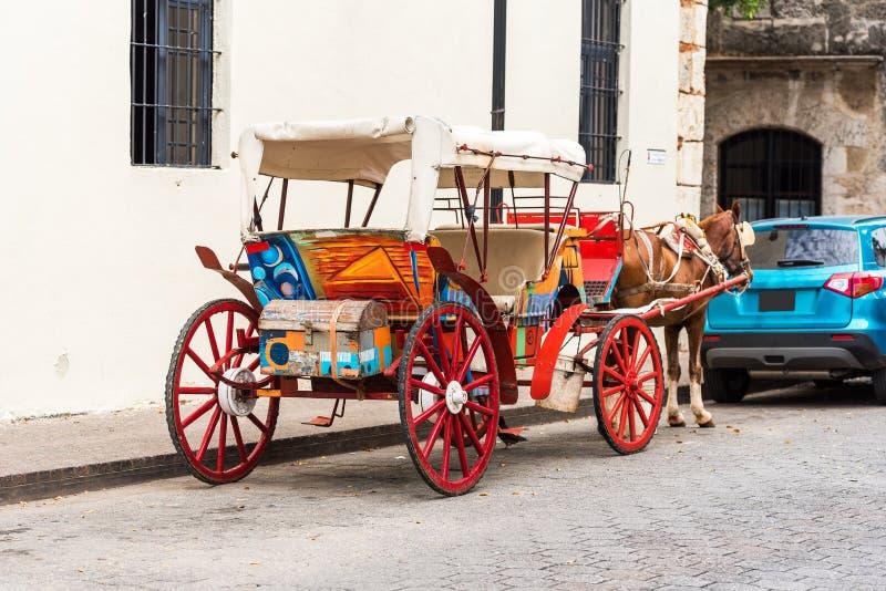 有一匹马的减速火箭的支架在一条城市街道上在圣多明哥,多米尼加共和国 复制文本的空间 免版税库存图片