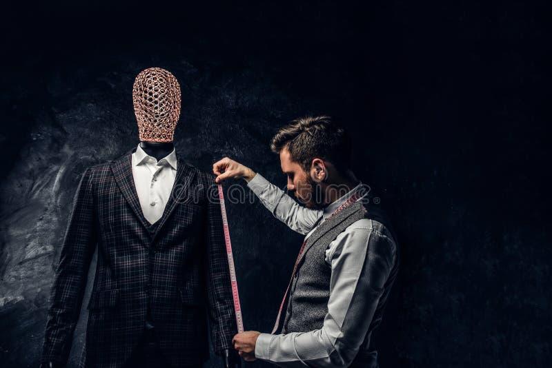 有一卷测量的磁带的一时尚编辑检查一套定制的典雅的人的衣服的袖子的长度在黑暗的 库存图片