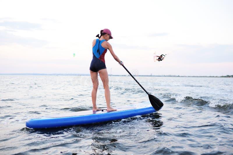 有一口板的女孩在海和日落的背景 免版税库存照片