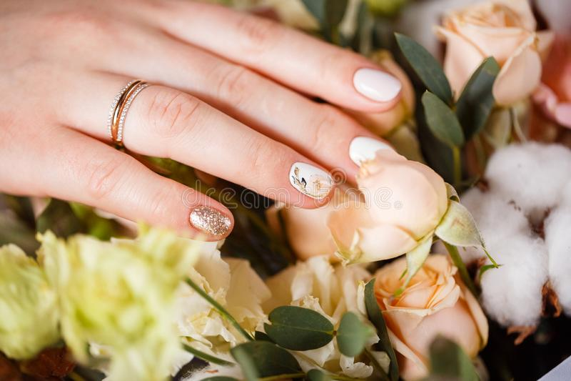 有一句美好的柔和的修指甲谎言的妇女的手指在花束 免版税库存照片