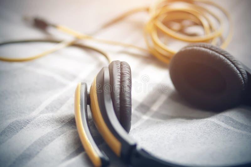 有一句话筒谎言的黄色黑耳机在一条灰色毯子 免版税库存照片