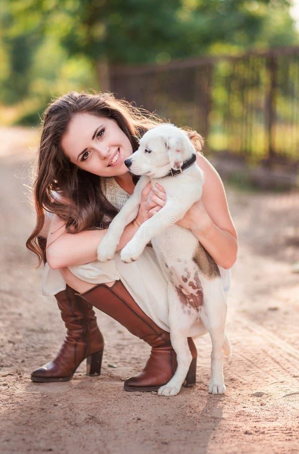 有一只小狗的时髦的女孩在她的手上 免版税图库摄影