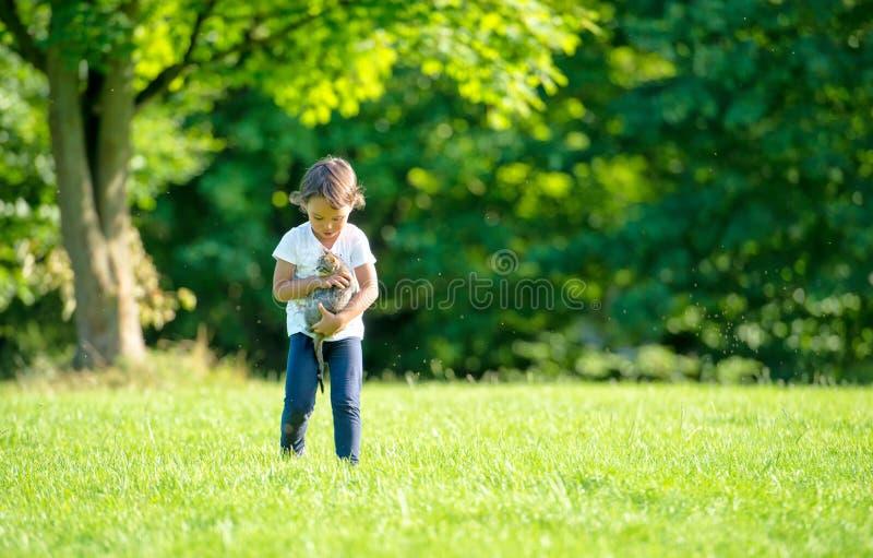 有一只猫的小女孩在公园 免版税库存照片