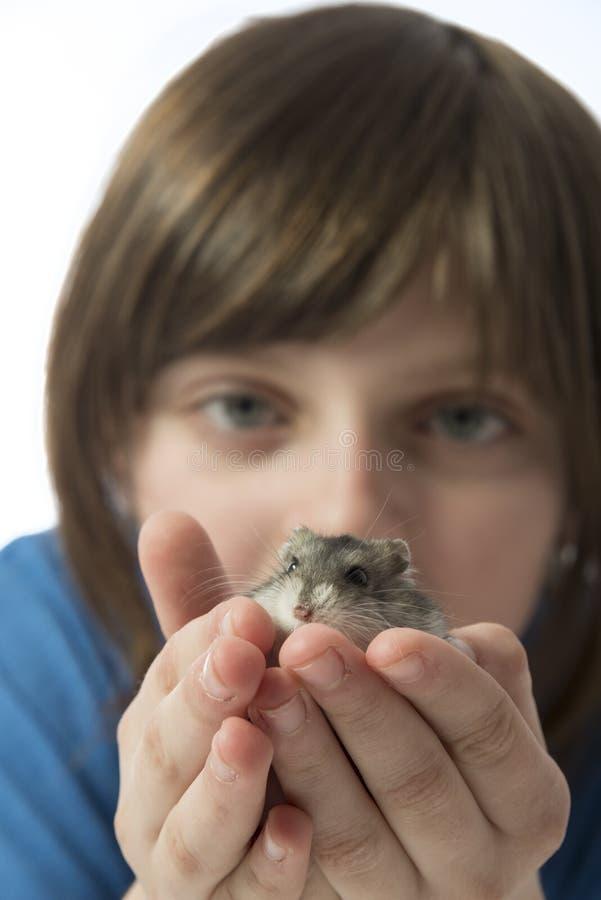 有一只逗人喜爱的仓鼠的一个愉快的litle女孩 免版税库存图片