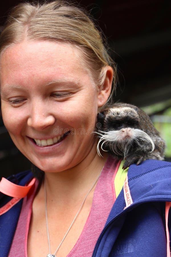 有一只逗人喜爱的小的猴子的妇女在她的肩膀 库存图片