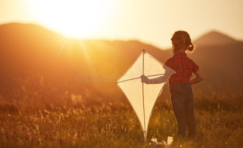 有一只风筝的愉快的儿童女孩在草甸在夏天 免版税库存照片