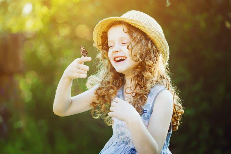 有一只蝴蝶的笑的卷曲女孩在他的手上 愉快的childhoo 库存照片