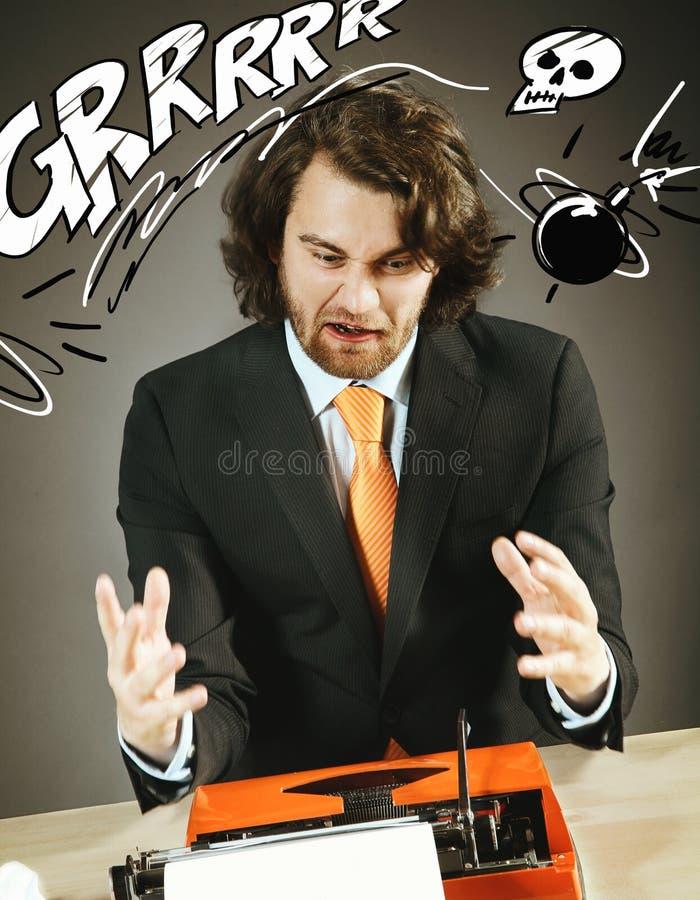 有一台古板的打字机的恼怒的人 免版税库存照片