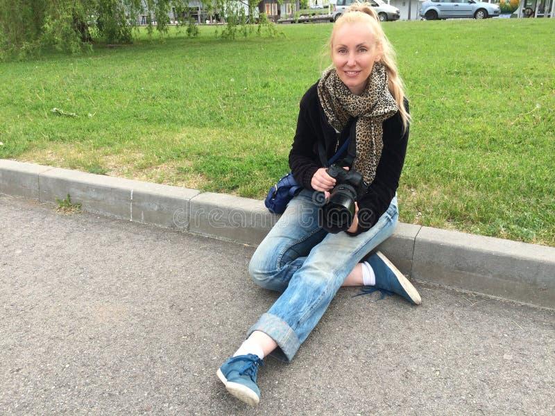 有一台大镜子照相机的年轻愉快的妇女坐草坪由路 免版税库存图片