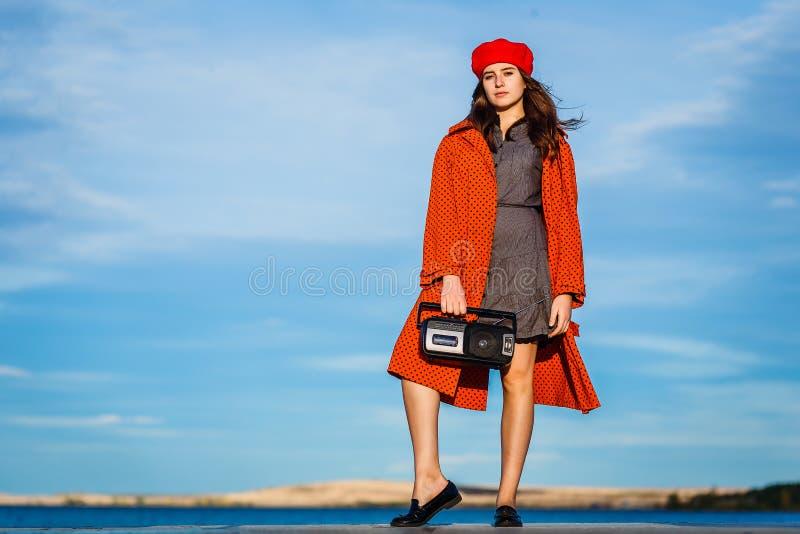 有一台录音机的十四岁的青少年的女孩在她的手上是在充分的成长在秋天 免版税库存照片