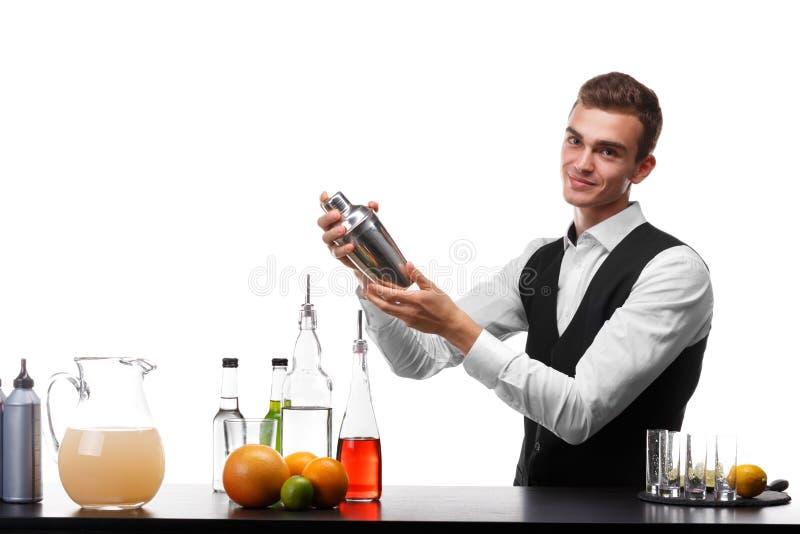 有一台振动器的一位可爱的侍酒者在酒吧柜台,石灰,桔子,在白色背景的柠檬 免版税图库摄影