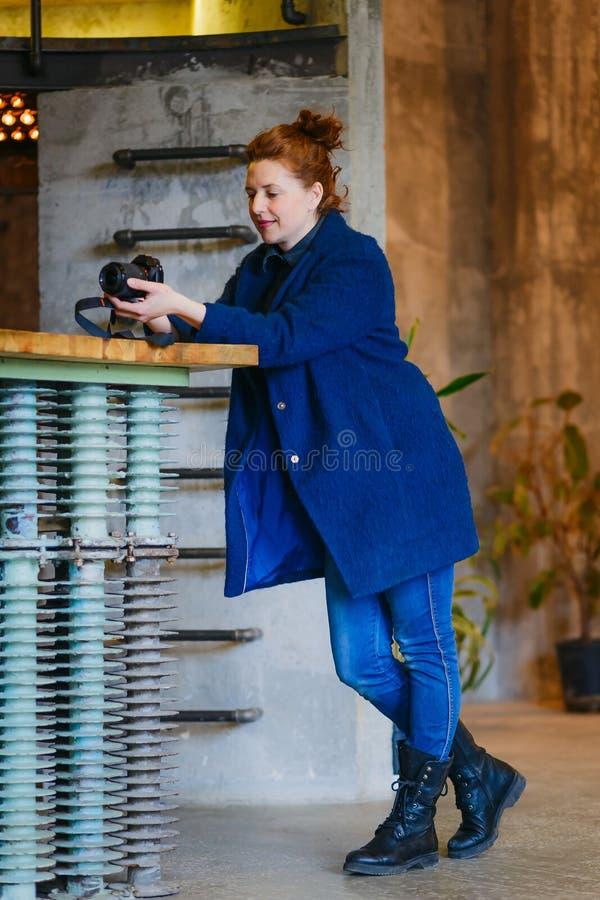 有一台照相机的妇女摄影师在一个全长演播室 图库摄影