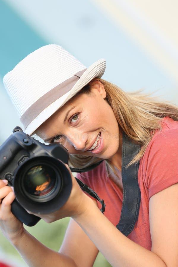 有一台照相机的妇女摄影师在工作 免版税库存图片
