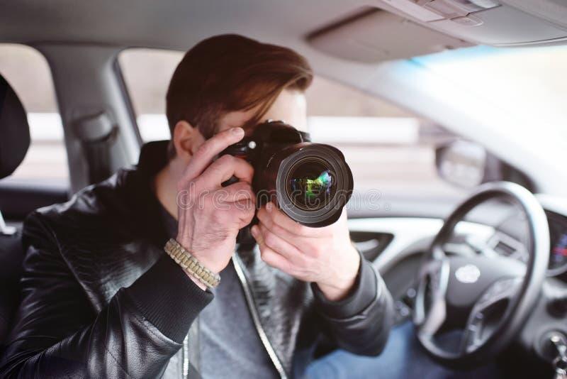 有一台照相机的年轻人在汽车 图库摄影