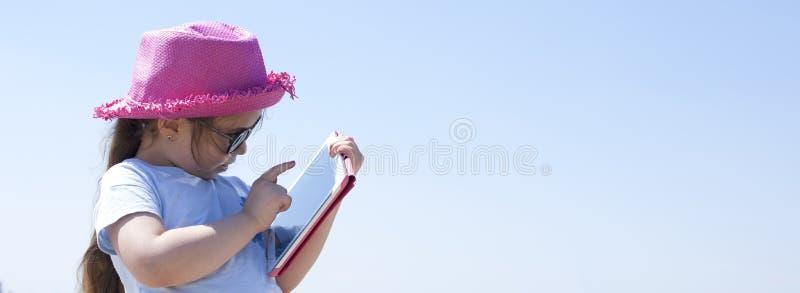 有一台片剂计算机的小女孩在手上 在海滩和蓝天的晴天 复制空间 钞票 免版税库存图片