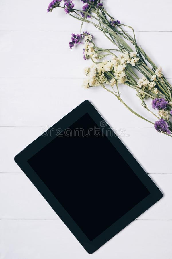 有一台空的黑屏显示器的特写镜头片剂与在白色桌背景的一花束与自然木葡萄酒 免版税库存照片