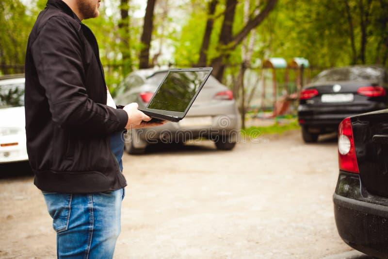 有一台膝上型计算机的专业人在汽车调整调整的控制系统 免版税库存图片