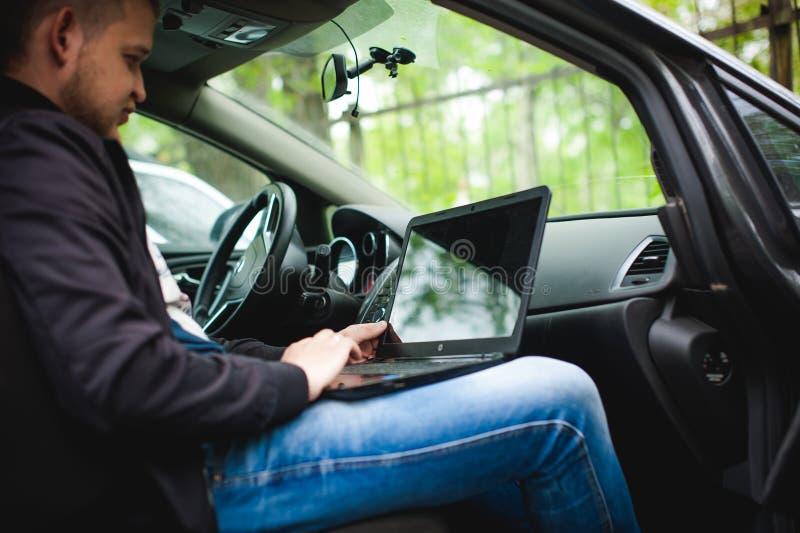 有一台膝上型计算机的专业人在汽车调整调整的控制系统 免版税图库摄影