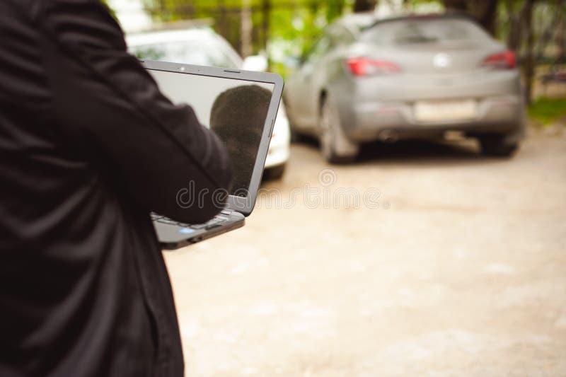 有一台膝上型计算机的专业人在汽车调整调整的控制系统 库存照片