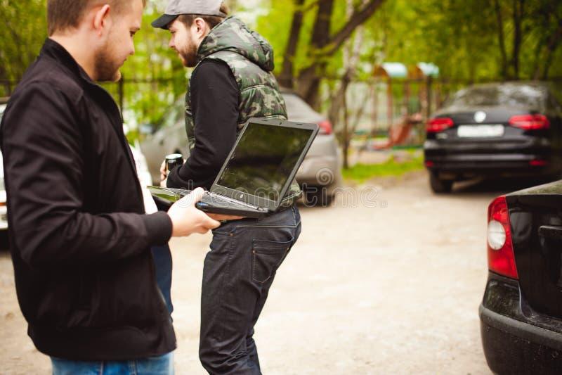 有一台膝上型计算机的人在停车场在汽车附近的围场做着与网络系统的操作 库存照片