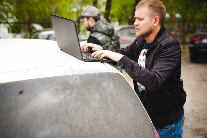 有一台膝上型计算机的人在停车场在汽车附近的围场做着与网络系统的操作 图库摄影