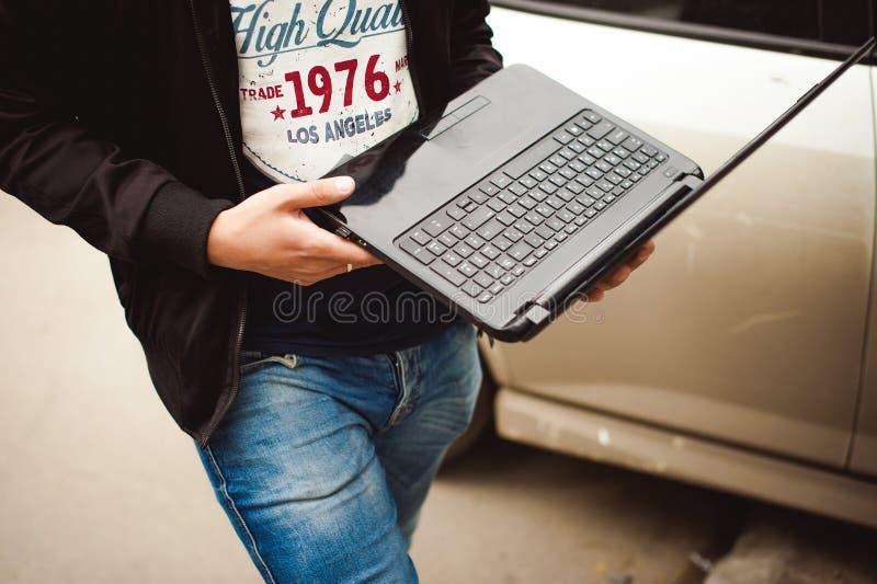 有一台膝上型计算机的人在停车场在汽车附近的围场做着与网络系统的操作 免版税库存图片