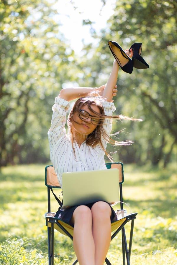 有一台膝上型计算机的女商人在公园坐与她的鞋子的一把折叠椅在她的手上 库存图片