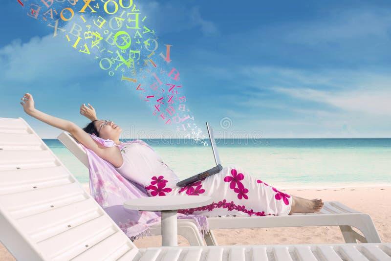 有一台膝上型计算机的少妇在热带海滩 免版税库存图片