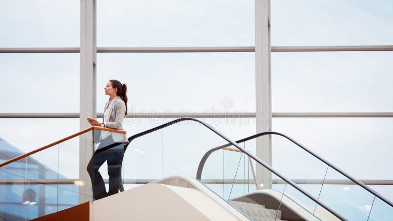 有一台膝上型计算机的年轻女人在她的手上在商业中心,一个现代明亮的办公室 事业和工作 免版税库存照片