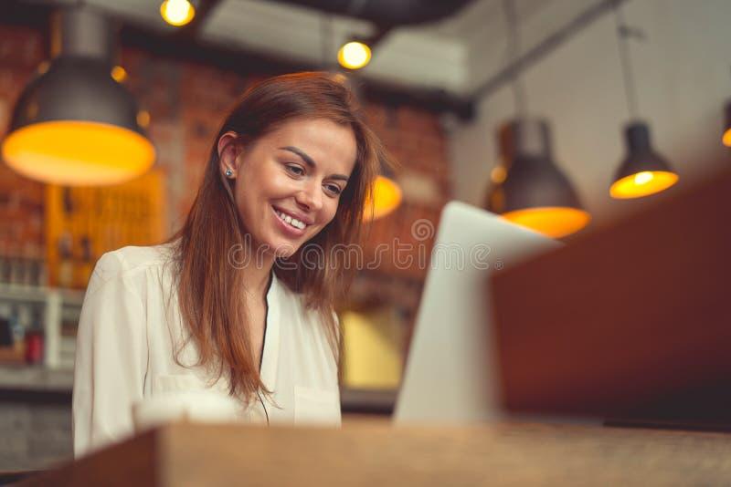有一台膝上型计算机的微笑的少妇在工作 库存照片