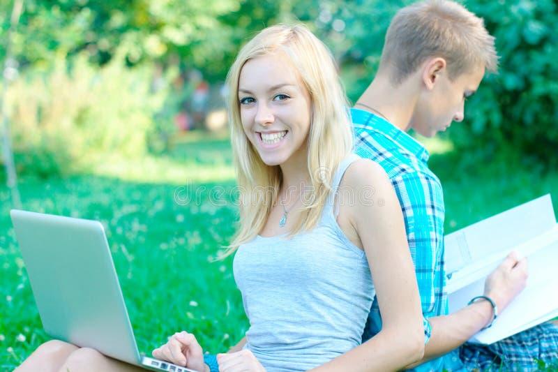 有一台膝上型计算机的愉快的女孩在公园 免版税库存图片
