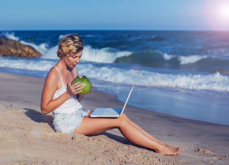 有一台膝上型计算机的美丽的偶然妇女在与海的海滩我 免版税库存照片