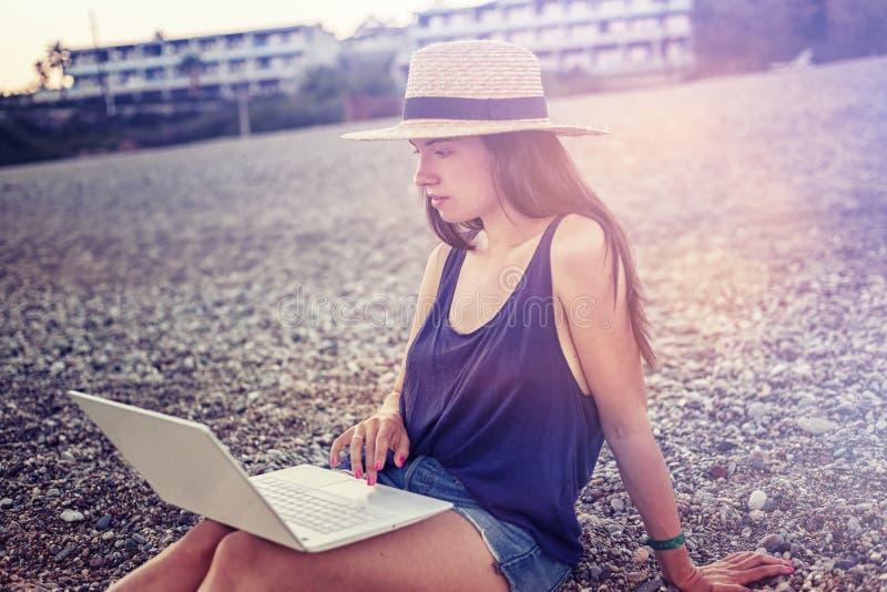 有一台膝上型计算机的美丽的少妇在日落的海滩 库存照片