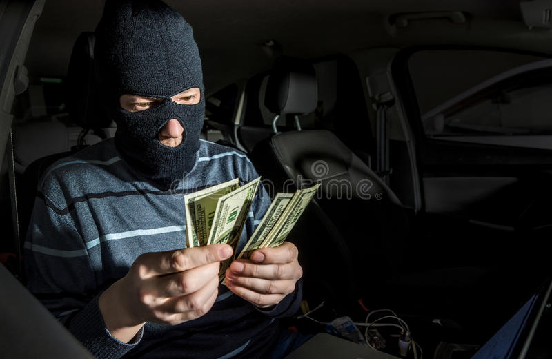有一台膝上型计算机的黑客在汽车里面 库存图片