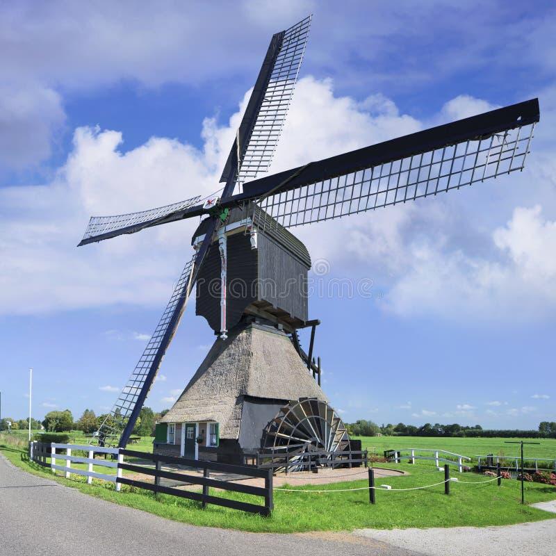 有一台水车的反对蓝天,荷兰木排水设备风车 图库摄影