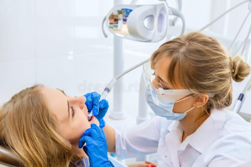 有一名女性患者的年轻职业妇女牙医 免版税库存图片