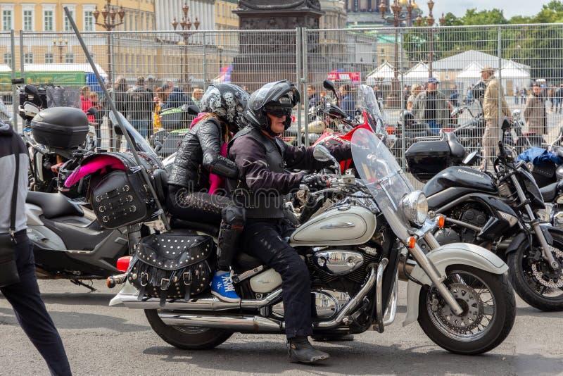 有一名妇女的人盔甲的坐一辆经典铃木摩托车 库存照片