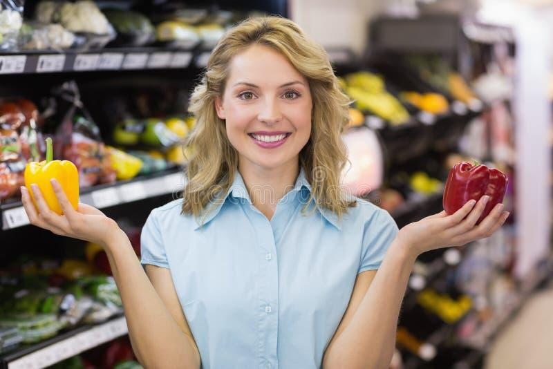 有一名微笑的白肤金发的妇女的画象在她的手上的一棵菜 免版税库存图片