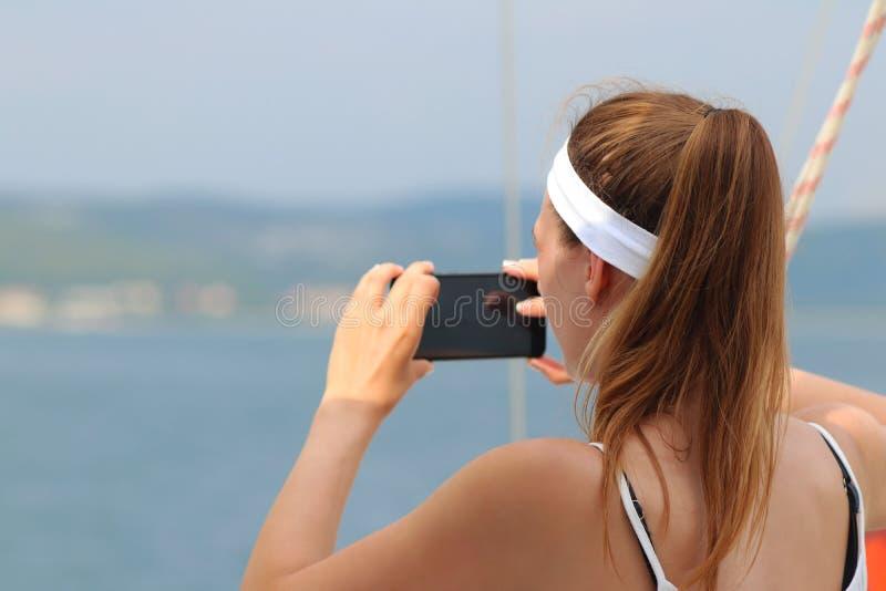 有一名棕色毛发的妇女的一个年轻美丽的女孩拍一个智能手机的照片在海的从航行游艇的边 一fasc 库存图片