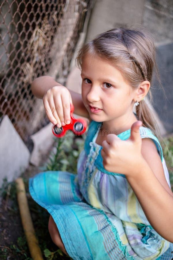 有一名锭床工人的愉快的矮小的农村女孩在她的手上 免版税库存图片