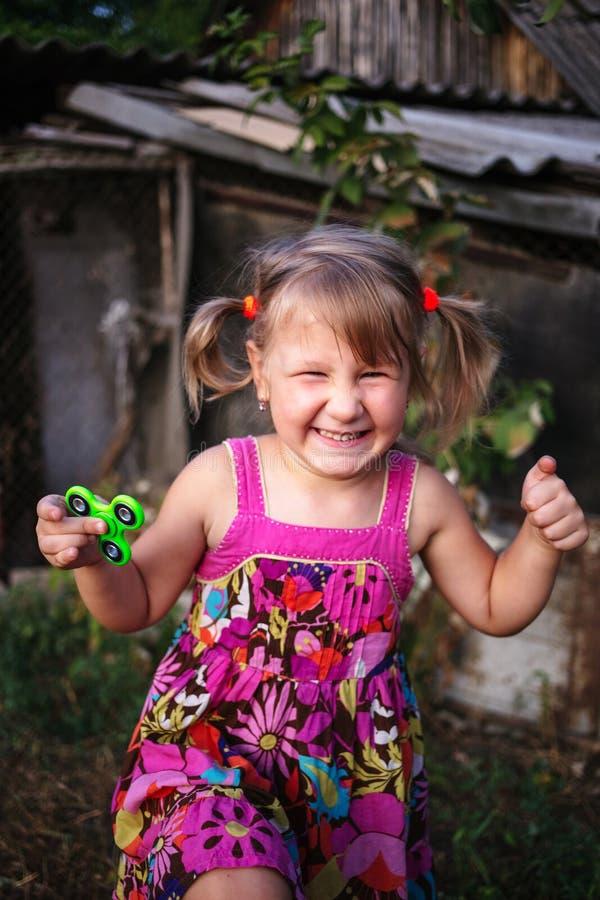 有一名锭床工人的愉快的矮小的农村女孩在她的手上 免版税库存照片