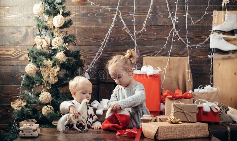 有一圣诞礼物的孩子在木背景 冬天孩子 孩子享受假日 r 新年孩子 免版税库存照片
