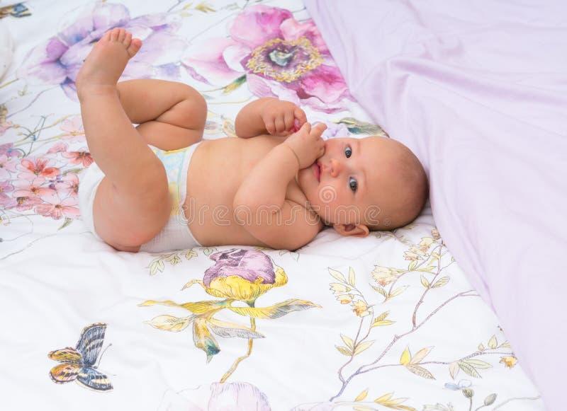 有一块干净的尿布的愉快的矮小的女婴 免版税库存图片