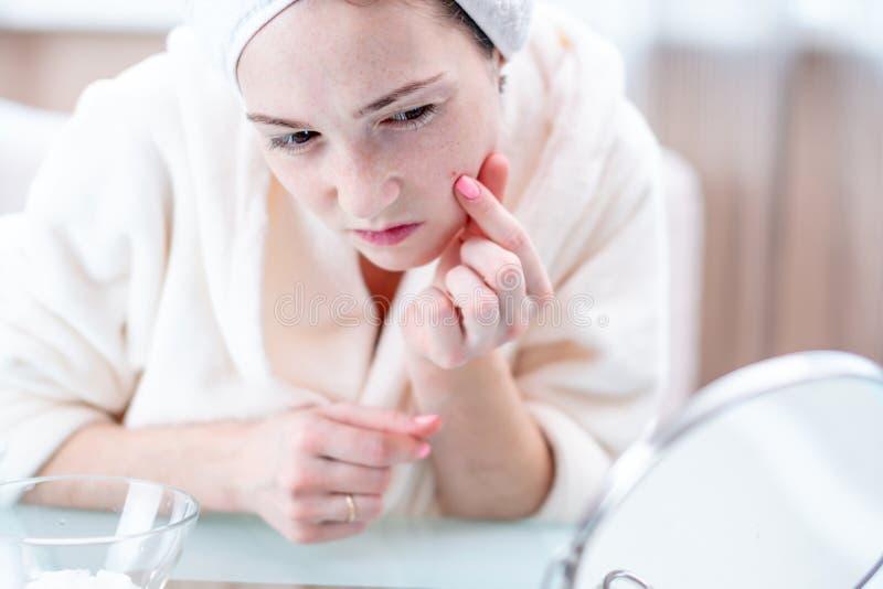 有一块毛巾的不快乐的年轻女人在她的头查出在她的面孔的粉刺 卫生学和喜欢的概念皮肤 库存照片