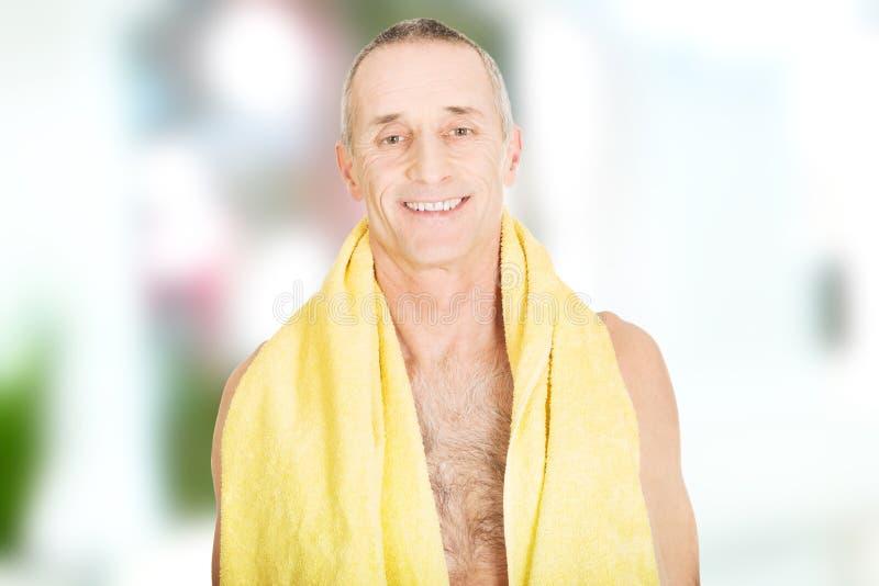 有一块毛巾的成熟人在脖子上 库存图片