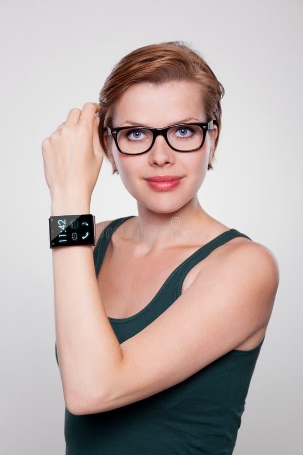 有一块现代互联网巧妙的手表的女孩在灰色背景 免版税库存照片