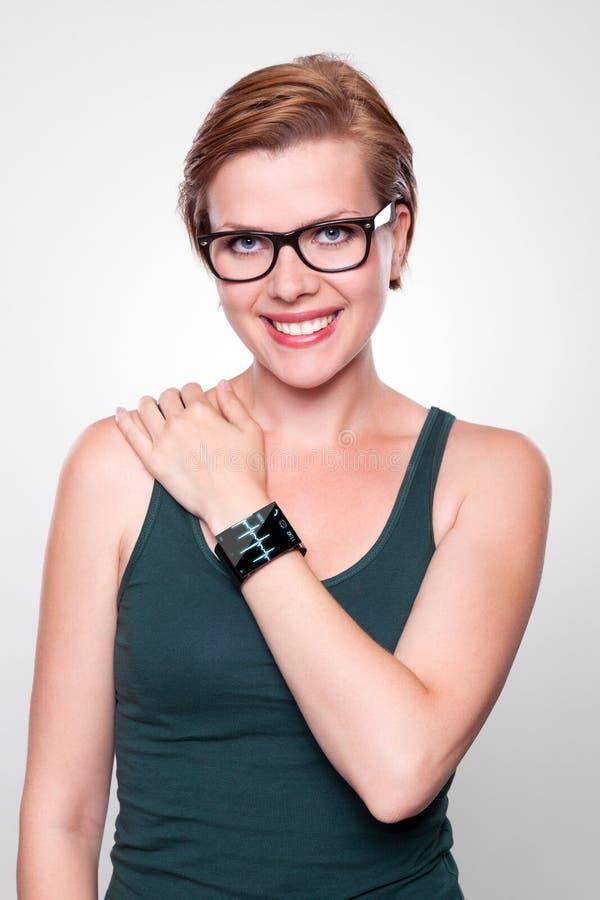 有一块现代互联网巧妙的手表的女孩在灰色背景 库存图片