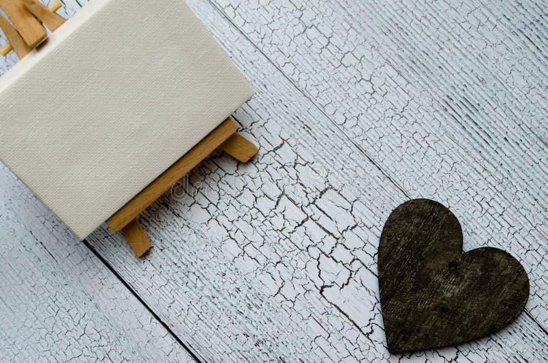有一块空白的帆布的小画架在白色和黑暗的木心脏 老木背景和大拷贝空间您的标志的 免版税库存照片