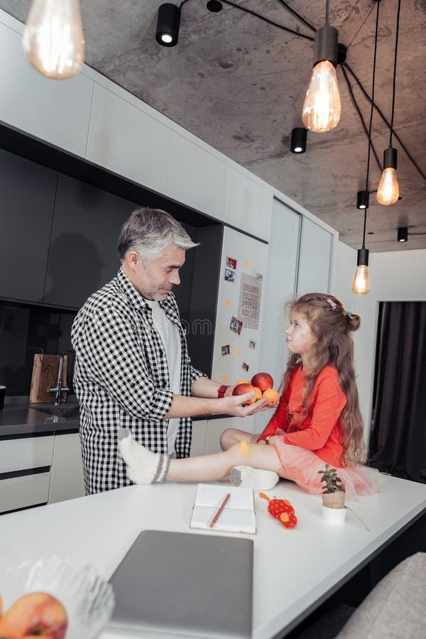 有一块红色手表的父亲在他的接触他的女儿头发的手上 库存图片
