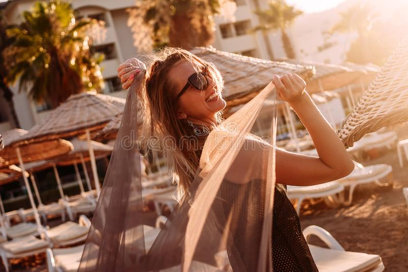 有一块轻的布料的年轻微笑的妇女在海滩的塑造外形的阳光下 免版税库存照片